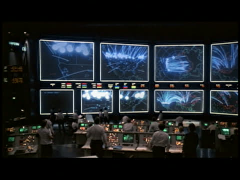 Medium shot dark control room w/screens w/maps in background tracking targets / people looking at screens