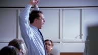 Medium shot day trader finishing phone call / standing up / climbing onto desk and dancing around