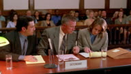 Medium shot defendant giving lawyer document / female lawyer standing and objecting / lawyers + client talking