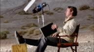 Medium shot director sitting in director's chair on desert film set / putting feet up with script in lap / Red Rock Canyon State Park, California