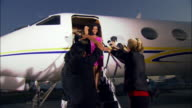 Medium shot Diva exiting private airplane, posing for paparazzi photographers and talking to journalist / Long Beach, California, USA