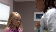 Medium shot doctor letting patient listen to her heartbeart with stethoscope / doctor listening to girl's heartbeat