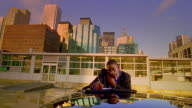 Medium shot dolly shot Black businessman talking on celluar phone and writing on car roof with Toronto skyline in background