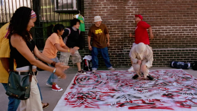 Medium shot dolly shot breakdancers performing on graffiti surface / others watching and clapping / Los Angeles, CA