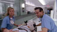 Medium shot dolly shot gurney point of view of patient being wheeled through hospital by doctors