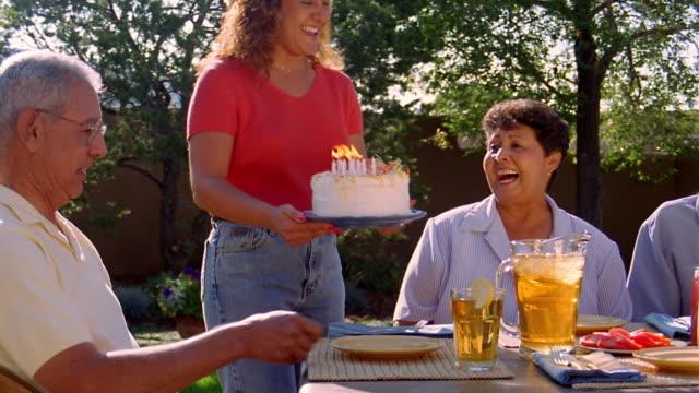 Medium shot dolly shot Hispanic woman bringing cake with candles to older couple sitting at table outdoors / Santa Fe