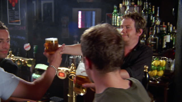 Medium shot dolly shot male bartender serving glasses of beer to three men sitting at bar / toasting and drinking