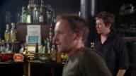Medium shot dolly shot male bartender standing against pillar in pub / three men near bar talking and ordering drinks