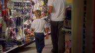 Medium shot dolly shot man and two boys picking up tools at hardware store