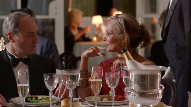 Medium shot dolly shot mature wealthy couple in eveningwear having dinner in fancy restaurant / toasting with champagne