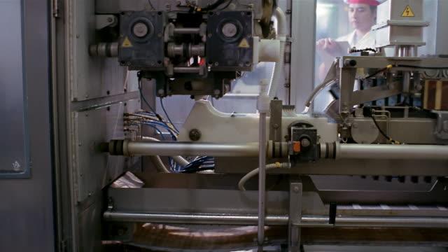 Medium shot dolly shot milk cartons on conveyor belt at Ultra Jaya milk processing plant/ technician in background/ Indonesia