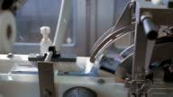 Medium shot dolly shot milk cartons on conveyor belt at Ultra Jaya milk processing plant / Bandung, Indonesia