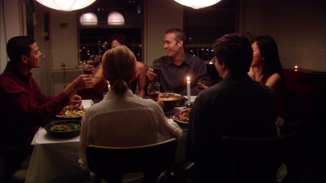 Medium shot dolly shot people toasting wine at dinner party