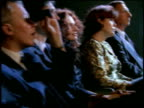 Medium shot dolly shot rows of audience in formalwear watching show intently in theater and clapping