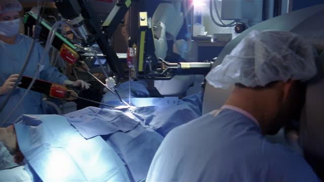 Medium shot dolly shot surgeon sitting at console and woman positioning robotic arms during robotic surgery