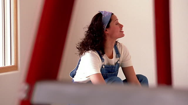 Medium shot dolly shot tilt up woman sitting and talking with man painting wall