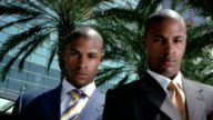 Medium shot dolly shot twin men wearing suits / looking off in opposite directions