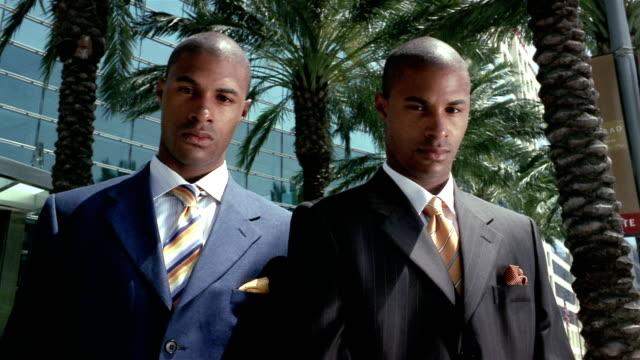 Medium shot dolly shot twin men wearing suits