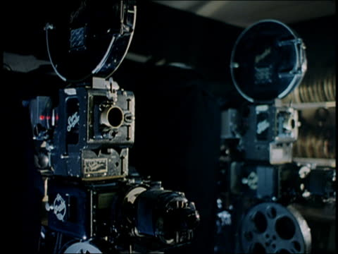 Medium shot dolly shot two film projectors / zoom in lens of projector w/light turning on