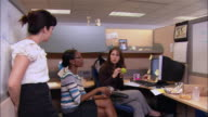 Medium shot dolly shot two women having working lunch in cubicle / co-worker joining them / sharing potato chips