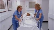 Medium shot dolly shot two women wearing scrubs wheeling woman on gurney down hospital hallway / turning into room