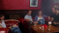 Medium shot dolly shot two young men and women sitting in bar in sofa's + drinking + talking w/red wall in background