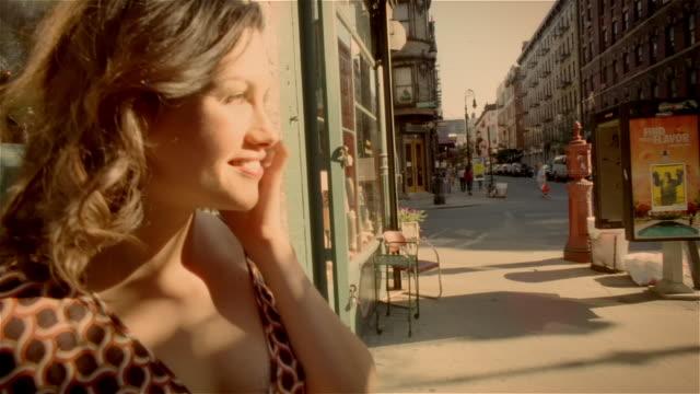 Medium shot dolly shot woman talking on cell phone on street corner / Lower East Side, New York City