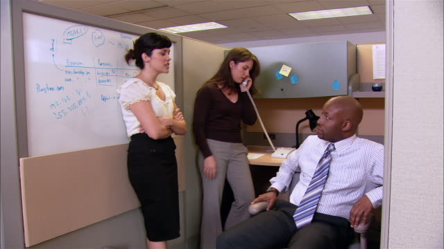 Medium shot dolly shot woman talking on phone in background as man and woman chat in cubicle
