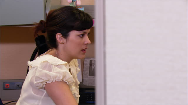 Medium shot dolly shot woman talking to co-worker and taking notes in cubicle
