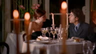 Medium shot dolly shot young couple in evening wear having dinner in fancy restaurant