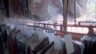 Medium shot dry cleaned garments in plastic bags moving along rack on hooks