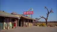 Medium shot entrance of motel with red neon sign on roof