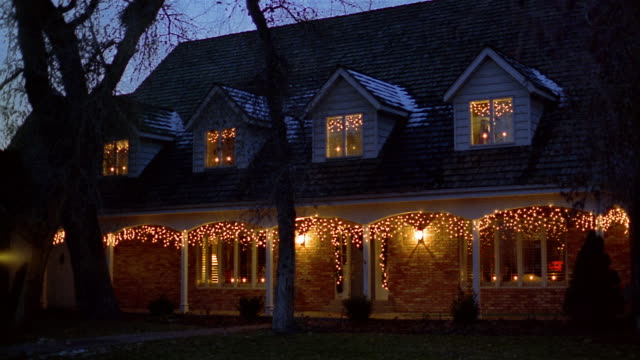 Medium shot exterior of house decorated with Christmas lights