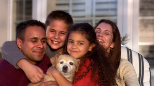 Medium shot family and dog posing outdoors