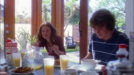 Medium shot family eating breakfast at table / brother and sister laughing