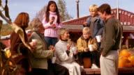 Medium shot family eating donuts and talking at pumpkin orchard