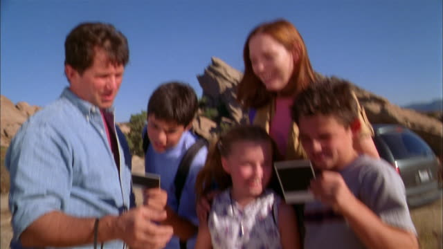 Medium shot family looking at instant photos on desert hiking trip