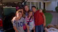 Medium shot family posing by SUV and smiling at CAM