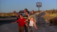 Medium shot family standing by parked minivan near Route 66 highway sign and looking at CAM + smiling / waving