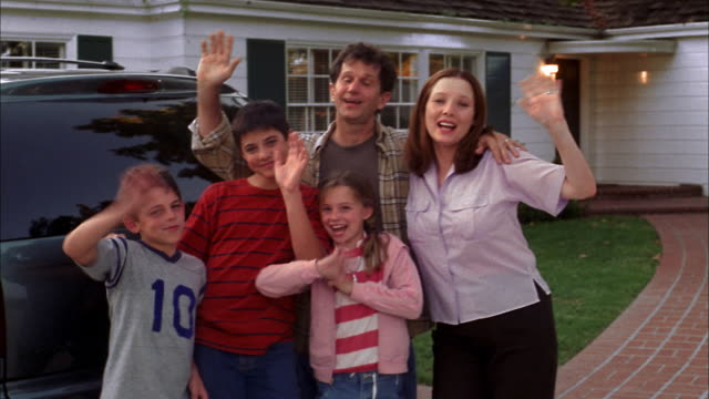 Medium shot family standing in front of house and waving to CAM