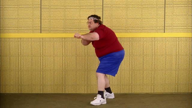 Medium shot fat man doing karate pose
