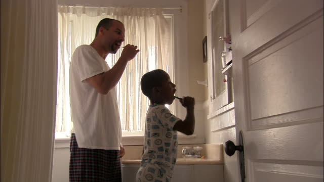 Medium shot father and son brushing teeth in morning