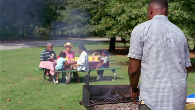 Medium shot father barbecuing hamburgers during picnic in park / family sitting at picnic table in background