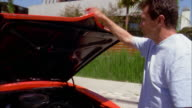 Medium shot father closing hood of sports car and handing car keys to his son / son getting into driver's seat