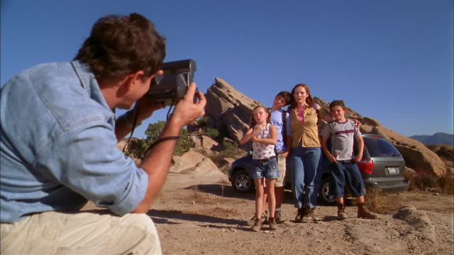 Medium shot father crouching and taking photo of family on rocky hiking trail
