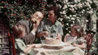1936 medium shot father eating piece of birthday cake at table with family at birthday party for four-year-old