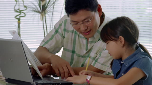 Medium shot father helping daughter with homework / hugging and kissing her