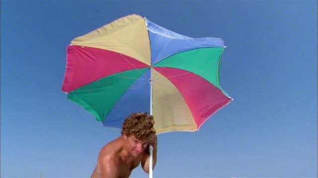 Medium shot father putting beach umbrella in sand w/extreme close up boy's eye in CAM foreground