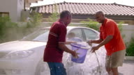 Medium shot father scolding two sons after washing car / smiling and getting into water fight with sons
