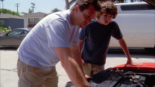 Medium shot father showing son parts of car engine under propped hood